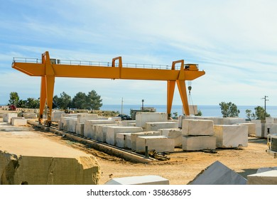 Industrial marble quarry, with cut blocks and workers and machines bulldozer at work / Industrial Marble Quarry