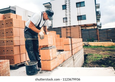 Industrial mason on construction site working with bricks and building walls. masonry details