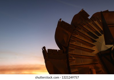 Industrial mining reclaimer bucket wheels with sunrise at the background construction mine site Perth, Australia