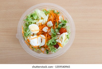 Industrial mixed salad with boiled egg, surimi, cherry tomato, grated carrot and lettuce
