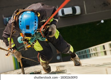 Industrial mountaineering worker hangs over residential building while washing exterior facade glazing. Rope access laborer hangs on wall of house. Concept of urban works. Copy space