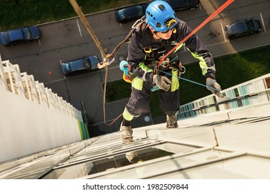 Industrial mountaineering worker hangs over residential facade building while washing exterior facade glazing. Rope access laborer hangs on wall of house. Concept of urban works. Copy space for site