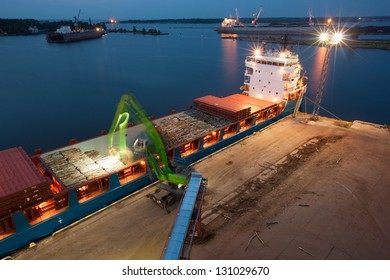 Industrial night at port - crane is loading ship for transportation