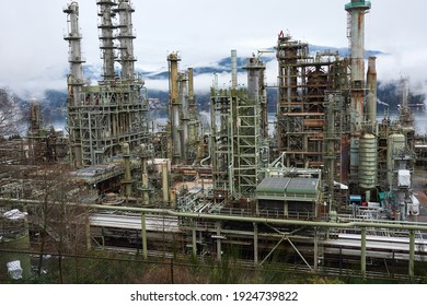 Industrial object refining oil and other toxic materials, working and steaming on a gloomy day, refinery processing oil into gas and fuel. Energy industry structure, loud and ugly looking.