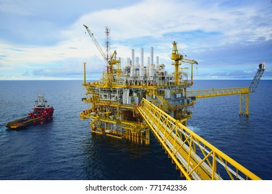 Industrial Offshore oil and gas rig platform with beautiful sky in the gulf of Thailand.Supply boat with blue and orange and white color sailing on open sea.Offshore crane.