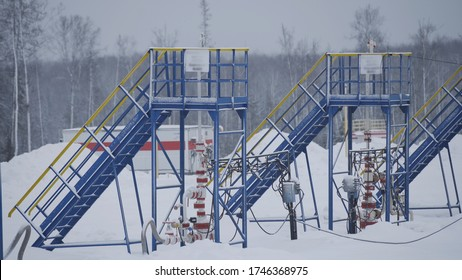 Industrial oil electric centrifugal pumps working and pumping crude oil for fossil fuel energy with drilling rig in oil field in winter. Equipment for wellhead connection oil well.