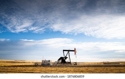 An industrial oil pump jack working on farm land under a morning sky in Rocky View County Alberta Canada.