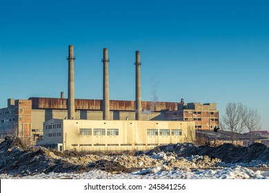 Industrial old building in winter time with tree funnels over blue sky in Belarus.