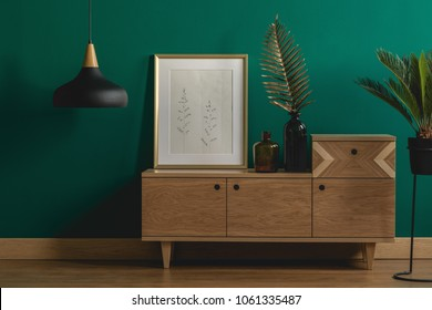 Industrial pendant light next to a stylish dresser and an art poster in a golden frame by a dark green wall of a modern bedroom interior