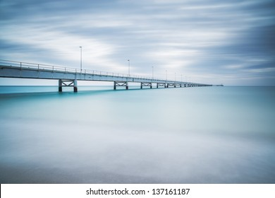 Industrial pier on the sea horizon. Side view. Long exposure photography in a cloudy day.