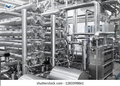 Industrial pipelines and modern equipment in cheese production interior