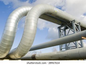 industrial pipelines on pipe-bridge against blue sky.