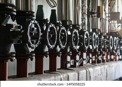 Industrial pipelines and valves with grey wheels in technical heating room.