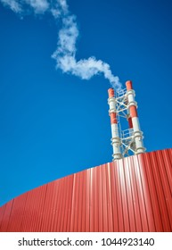 Industrial pipes and smoke on blue sky background