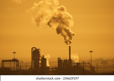 industrial plant with air pollution in a hazy orange sky