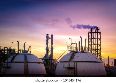 Industrial plant on sky sunset background, Gas storage sphere tank in petrochemical plant with smoke stacks at evening time