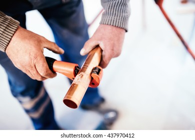 Industrial Plumber cutting a copper pipe with a pipe cutter.