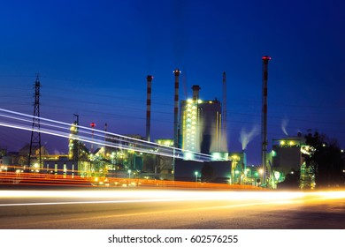 Industrial power plant with light traces of cars by night