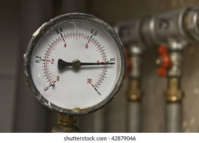 Industrial pressure meter - barometer and water pipes in the background