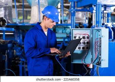 industrial programmer checking control box status with laptop computer