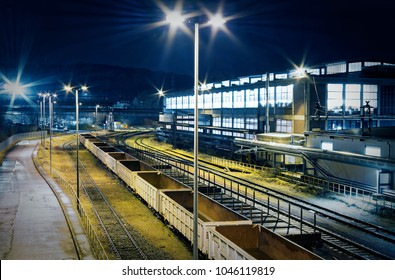 Industrial rail yard shunting station at night with many lights and wagons on a siding in an industrial plant