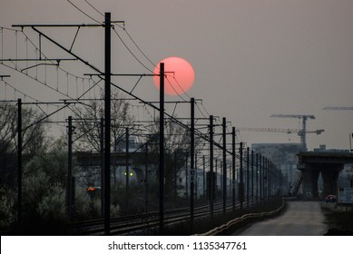 Industrial railway/Old industrial railway in the low light of the setting sun and a bridge under construction in the background.
