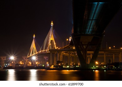The Industrial Ring Bridge shines at dusk in Thailand. The Bridge cross over ChaoPhraya River and Bangkok Harbor
