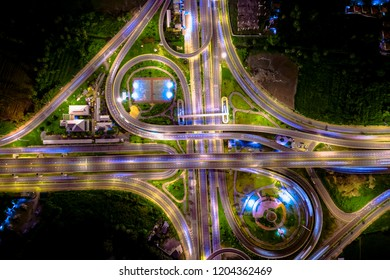 industrial ring road traffic car and motorway highway expressway in night time and lighting over colourful aerial top view from drone