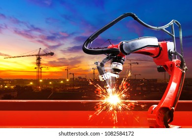 Industrial robot welder welding i beam steel structure construction by metal arc welding against construction site in beautiful sunset sky