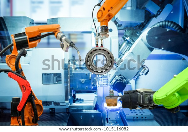 Industrial robotic welding and robot gripping working on smart factory, on machine blue tone color background, industry 4.0 and technology.