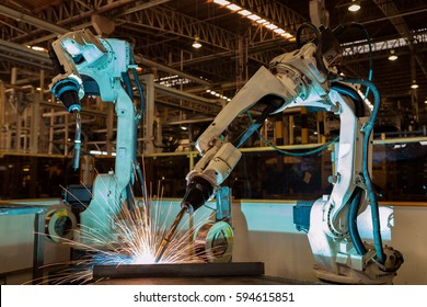 Industrial robots are welding in car factory