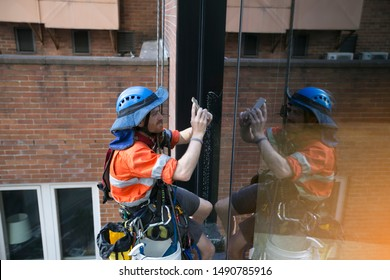 Industrial rope access abseiler inspector  wearing full safety harness, helmet fall protection abseiling conducting inspecting on windows using cell phone taking pic defect glass high rise building