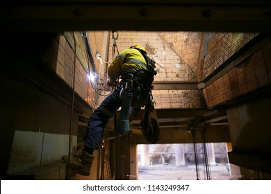 Industrial rope access abseiler welder wearing safety harness, abseiling commencing welding repairing at construction site, Perth, Australia