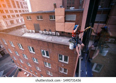 Industrial rope access abseiler window cleaner wearing full safety harness, helmet fall protection abseiling with twin low stretch ropes conducting cleaning window with yellow scraper Sydney CBD