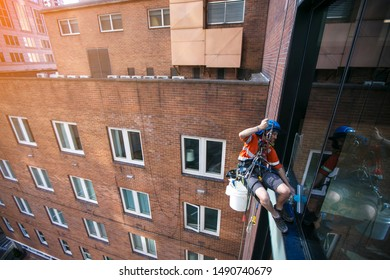Industrial rope access abseiler window cleaner wearing full safety harness, helmet fall protection abseiling with twin low stretch ropes conducting cleaning window Sydney CBD high rise building site