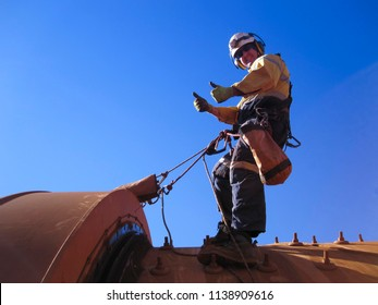 Industrial rope access fitters, boiler maker wearing safety harness using twin rope hanging top of the chute as fall arrest position giving a thumb up at construction mining site Perth, Australia