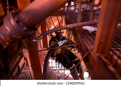 Industrial rope access miner fitter repair worker abseiling with static rope performing connecting installing hydraulic hose system into corner connecter at construction mine site Perth, Australia