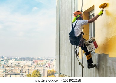 Industrial rope access worker hanging from the building while painting the exterior facade wall. Industrial alpinism concept image