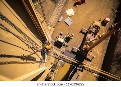 Industrial rope access worker welder working at height abseiling with low stretching rope performing structure wall  maintenance repair on construction mine site, Perth, Australia