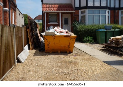 Industrial rubbish skip in front of house. Selective focus on full metal bin with space to add own text on surrounding background of driveway, wooden fence, houses. Renovate, moving, clearance concept