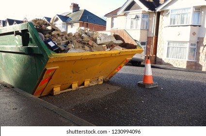 Industrial rubbish skip, left side of frame, for background use. Space to add text in front of the full metal bin, footpath, road surface. House renovating, construction building site removal concept.
