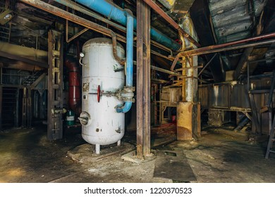 Industrial rusty pipeline and vats in underground cellar of abandoned factory.