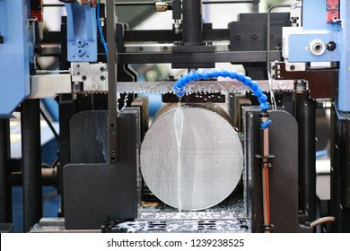 The industrial sawing machine cutting the steel rod with coolant fluid.The band saw machine cutting raw metals rods the with the coolant fluid.