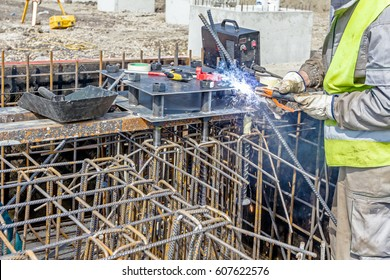 Industrial shot of construction worker who is welding metal frame, cage of armature inside of demountable wooden mold for concreting pillar base.