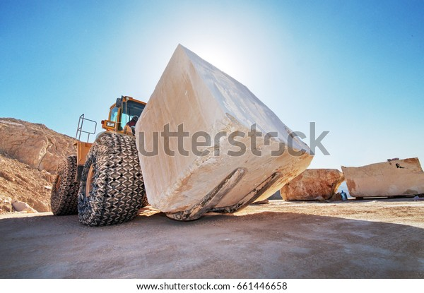 Industrial shot illustrating the production of marble. A bulldozer moving a huge marble block at a quarry.
