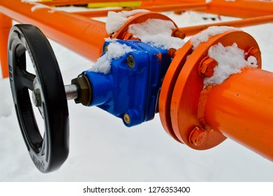 Industrial shut-off regulating protective pipe fittings. Black valve for opening, closing on an iron orange metal pipe with flanges, studs, nuts against the background of white snow in winter.