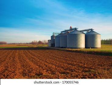 Industrial silos in the fields, in the sunset
