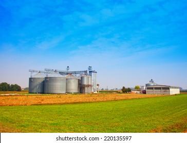 Industrial silos under blue sky, in the fields