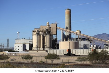 Industrial site with smoke pipe, elevator, delivery freight train cars and power lines running through blue sky