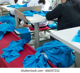Industrial size textile factory in asia, asian workers behind sewing machines.